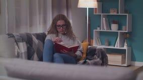 La mujer hermosa joven lee un libro de papel en su sala de estar acogedora por la tarde metrajes