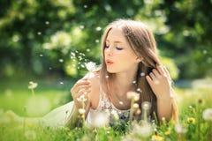 La mujer hermosa joven miente en una hierba Fotografía de archivo libre de regalías