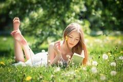 La mujer hermosa joven miente en una hierba y lee el libro Fotos de archivo