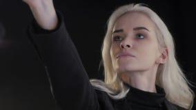 La mujer hermosa joven mira la reflexión Modelo del blonde de la manera Muchacha atractiva del estudiante almacen de video