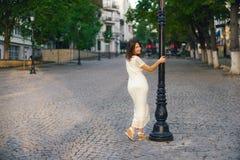 La mujer hermosa joven, oscuro-cabelluda, se opone con ella detrás al phonor en la calle en el centro de ciudad en un día soleado Fotografía de archivo libre de regalías