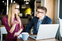 La mujer hermosa joven pregunta a hombre en el ordenador portátil con sonrisa y la discusión algo con su compañero de trabajo mie fotografía de archivo