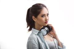 La mujer hermosa joven que escuchaba la música con los auriculares grandes aisló el fondo blanco Imagenes de archivo