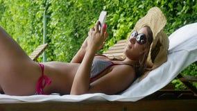 La mujer hermosa joven que lleva las gafas de sol, sombrero y un bikini se relaja en una silla de cubierta junto a una piscina y  metrajes