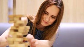 La mujer hermosa joven que saca el bloque de madera y falla la torre del edificio almacen de metraje de vídeo