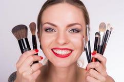 La mujer hermosa joven que se sostiene los cepillos acerca a su cara Imagenes de archivo