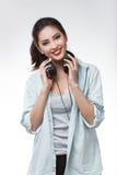 La mujer hermosa joven que sostenía los auriculares grandes aisló el fondo blanco Fotos de archivo libres de regalías