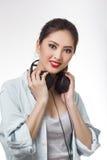 La mujer hermosa joven que sostenía los auriculares grandes aisló el fondo blanco Fotografía de archivo libre de regalías