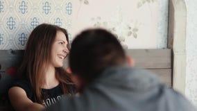 La mujer hermosa joven ríe mientras que ella habla con su hombre Los pares en amor tienen conversación mientras que se sientan en almacen de video