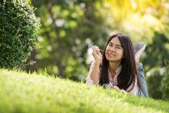 La mujer hermosa joven relajada con la cara sonriente goza el comer del palillo del cerdo en el parque Fotografía de archivo