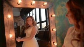 La mujer hermosa joven se atusa cerca del espejo con las lámparas almacen de metraje de vídeo