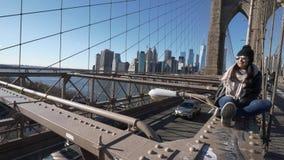 La mujer hermosa joven se relaja en el puente de Brooklyn mientras que disfruta de la visión asombrosa almacen de metraje de vídeo