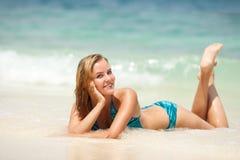 La mujer bonita joven se relaja en la arena en la playa Fotos de archivo