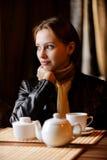 La mujer hermosa joven se sienta en café Foto de archivo
