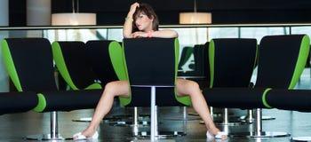 La mujer hermosa joven se sienta en silla en sitio del negocio Foto de archivo