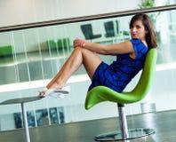 La mujer hermosa joven se sienta en silla verde en sitio del negocio Fotografía de archivo