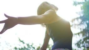 La mujer hermosa joven siente el aire libre libre, unido con la naturaleza, mira para arriba el cielo del sol almacen de metraje de vídeo