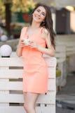 La mujer hermosa joven sostiene la taza de té en café Imagenes de archivo