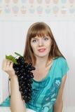 La mujer hermosa joven sostiene la uva negra Imagen de archivo libre de regalías