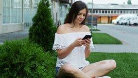La mujer hermosa joven utiliza el teléfono mientras que sienta en el césped cerca de las impresiones del hotel un mensaje almacen de video