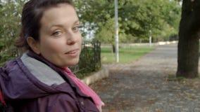 la mujer hermosa 4k camina lejos en un parque que vueltas, sonrisas y ondas almacen de metraje de vídeo