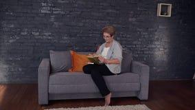 La mujer hermosa mayor se está sentando en el sofá y está leyendo el libro de la ficción almacen de metraje de vídeo