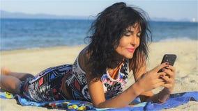 La mujer hermosa miente en la playa y ríe mensajes de la lectura en su teléfono móvil almacen de video
