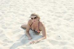 La mujer hermosa miente en una playa en arena Imágenes de archivo libres de regalías