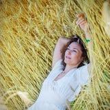 La mujer hermosa miente entre las espigas de trigo en el campo Fotografía de archivo