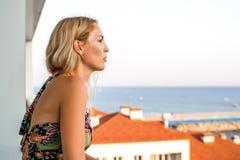 La mujer hermosa mira el mar del balkon del ` s del edificio fotografía de archivo libre de regalías