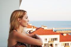 La mujer hermosa mira el mar del balkon del ` s del edificio imagenes de archivo