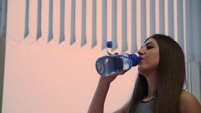 La mujer hermosa misma bebe el agua de una coctelera después de entrenar almacen de video