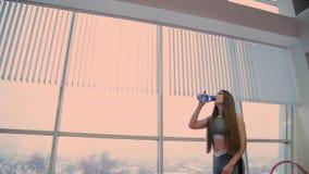 La mujer hermosa misma bebe el agua de una coctelera después de entrenar almacen de metraje de vídeo