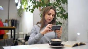 La mujer hermosa pasa su tiempo en un café: fotos de los rmakes para las redes sociales - café y libro