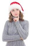 La mujer hermosa pensativa en ropa del invierno y el sombrero de santa sueñan Foto de archivo