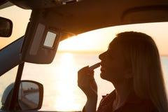 La mujer hermosa pinta sus labios en el coche Foto de archivo