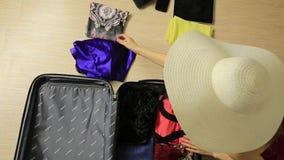 La mujer hermosa pone los vestidos en la maleta para el viaje almacen de metraje de vídeo