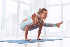 La mujer hermosa practica el asana Tittibhasana - actitud de la yoga de la posición del pino de la luciérnaga en el estudio de la imagen de archivo