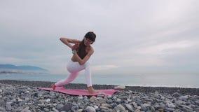 La mujer hermosa practica la yoga al aire libre almacen de metraje de vídeo