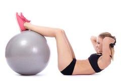 La mujer hermosa que hace el ABS ejercita con la bola de la aptitud Imagenes de archivo