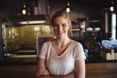 La mujer hermosa que se colocaba con los brazos cruzó en restaurante Fotografía de archivo libre de regalías