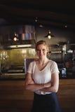 La mujer hermosa que se colocaba con los brazos cruzó en restaurante Fotografía de archivo
