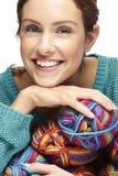 La mujer hermosa que se sienta con hilado rueda, sonriendo Foto de archivo libre de regalías