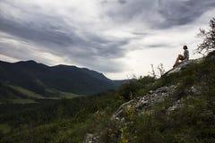 La mujer hermosa que se sienta en la montaña superior y que comtempla el cielo se nubla Foto de archivo libre de regalías