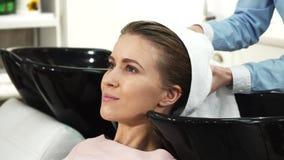 La mujer hermosa que sonreía consiguiéndole el pelo se secó por un peluquero profesional metrajes