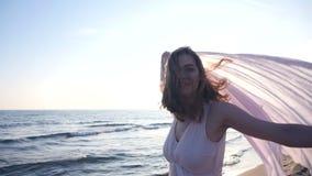 La mujer hermosa que sostiene la tela ligera en la playa y disfruta de la puesta del sol metrajes