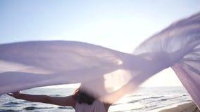 La mujer hermosa que sostiene la tela ligera en la playa y disfruta de la puesta del sol almacen de metraje de vídeo