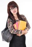 La mujer hermosa que sostiene un libro y lleva el bolso Foto de archivo libre de regalías