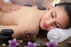 La mujer hermosa que tiene una salud detrás da masajes foto de archivo