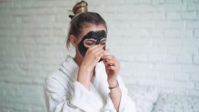 La mujer hermosa quita la máscara de limpiamiento de cara en el fondo blanco del ladrillo almacen de video